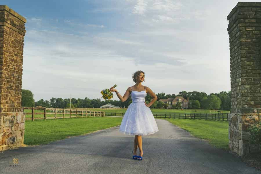 Bride standing in the drive way of the Manor at Carriage Farm posing for her bridal portrait