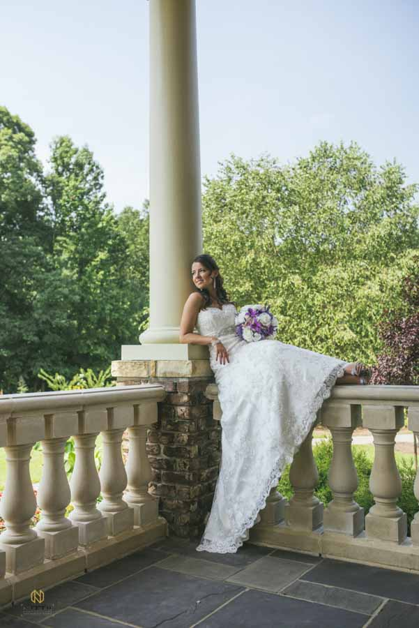 bride sitting on the stone veranda on the back porch at the Manor at Carriage Farm posing for her Raleigh bridal portrait