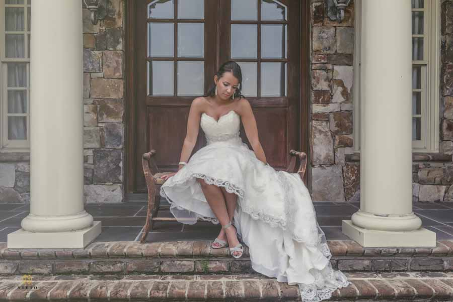 Bride sitting on the steps of the Manor at Carriage Farm with her legs crossed posing for her Raleigh bridal portraits