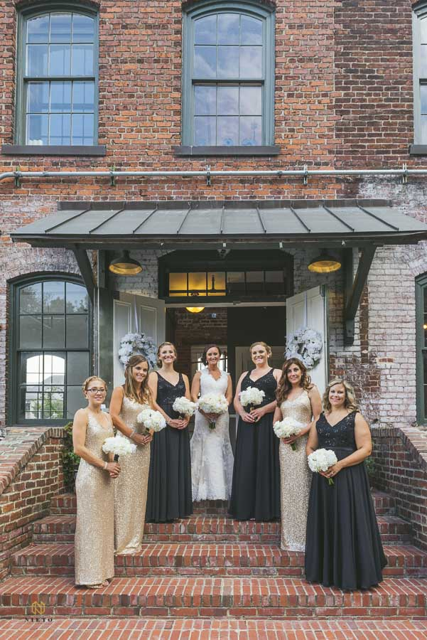 Bride and her bridal party dressed in gold and black dresses, posing on the stairs of Melrose Knitting Mill