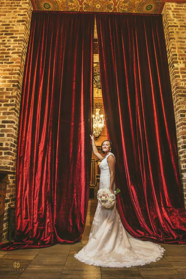 bride standing in front of the red curtains at Melrose Knitting Mill