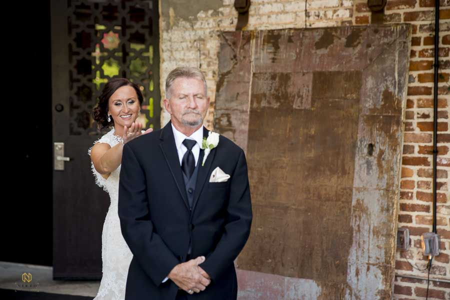 bride tapping her father on the shoulder during their first look