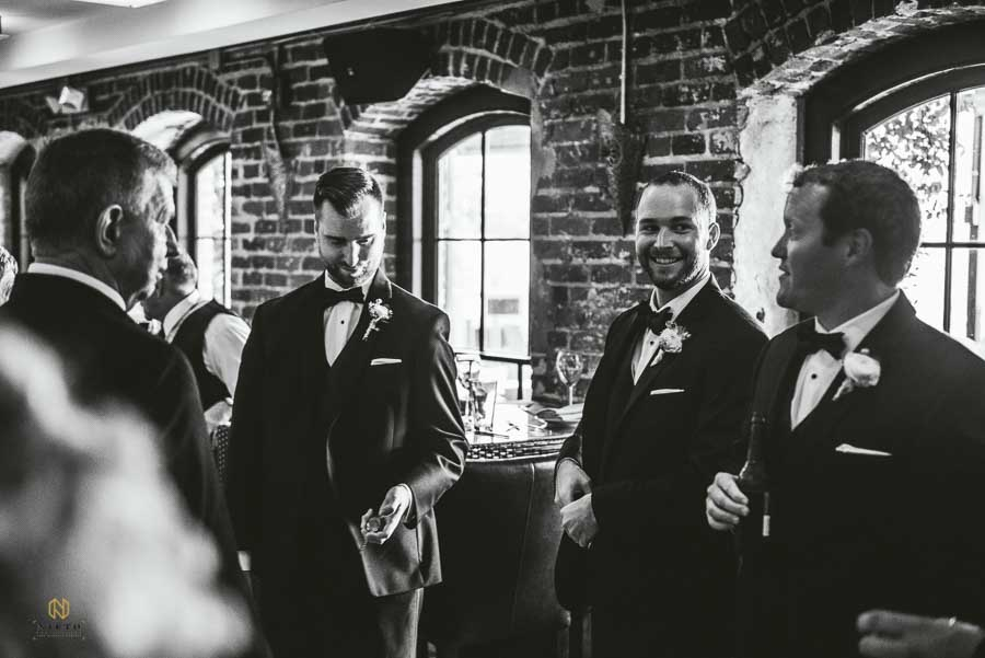 black and white image of the groom talking with his groomsmen