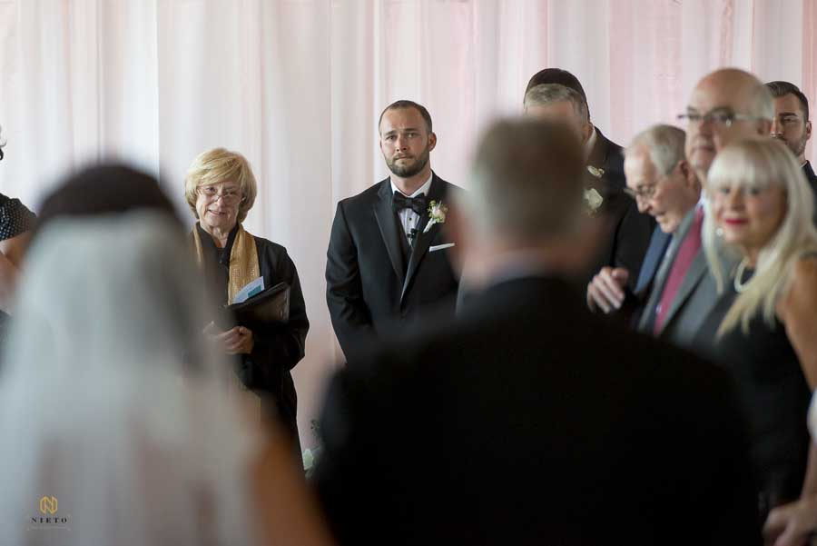 groom looking at the bride for the first time as she walks down the aisle