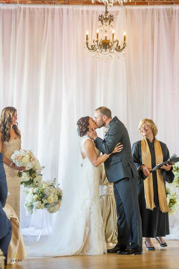 groom kissing for the first time as the minister and the maid of honor watch