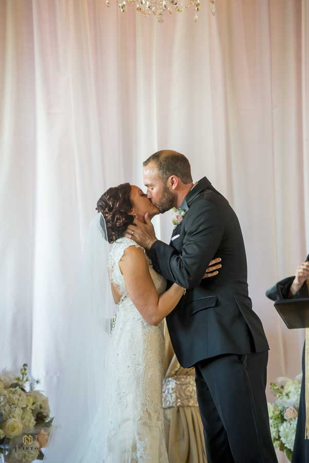 the groom grabbing the bride around her neck as they kiss for the first time at their Melrose Knitting Mill wedding