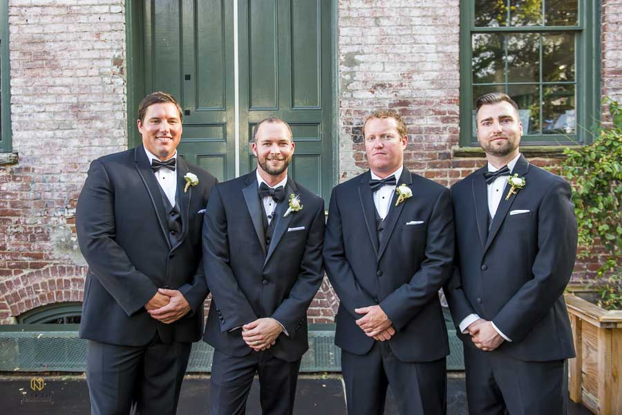 the groom and his groomsmen posing for a formal portrait at Melrose Knitting Mill