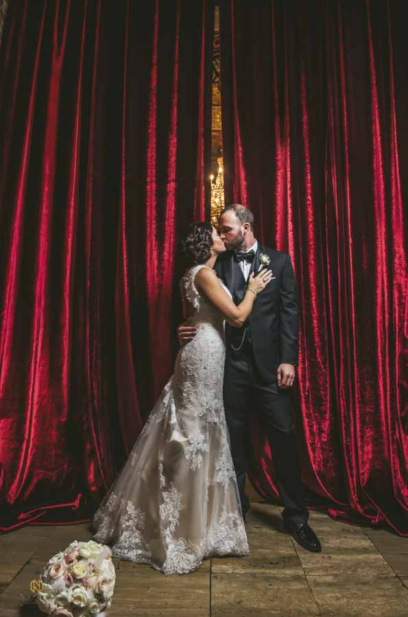 raleigh wedding photography of bride and groom kissing in front of the red curtains at Melrose Knitting Mill