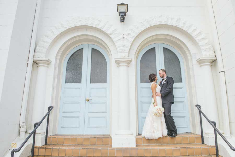 the groom putting his hands around the brides waist as the pose in front of the Vintage Church in Raleigh