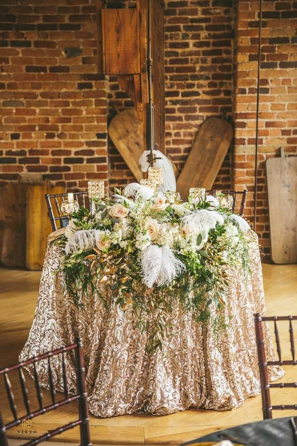 the sweet heart table at Melrose Knitting Mill decorated with an opulent floral piece and gold linen