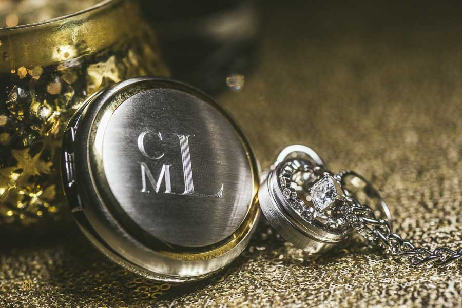 Grooms engraved pocket watch, wedding bands, and the brides engagement ring detail shot.