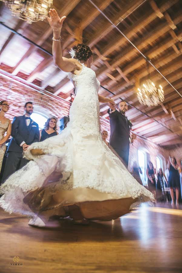 bride spinning in her wedding dress as she dances with the groom at Melrose Knitting Mill.