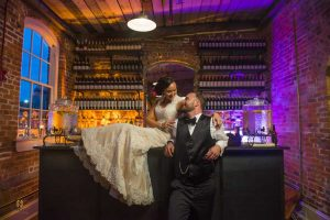 bride sitting on the bar as the groom stands beside her at their Melrose Knitting Mill wedding