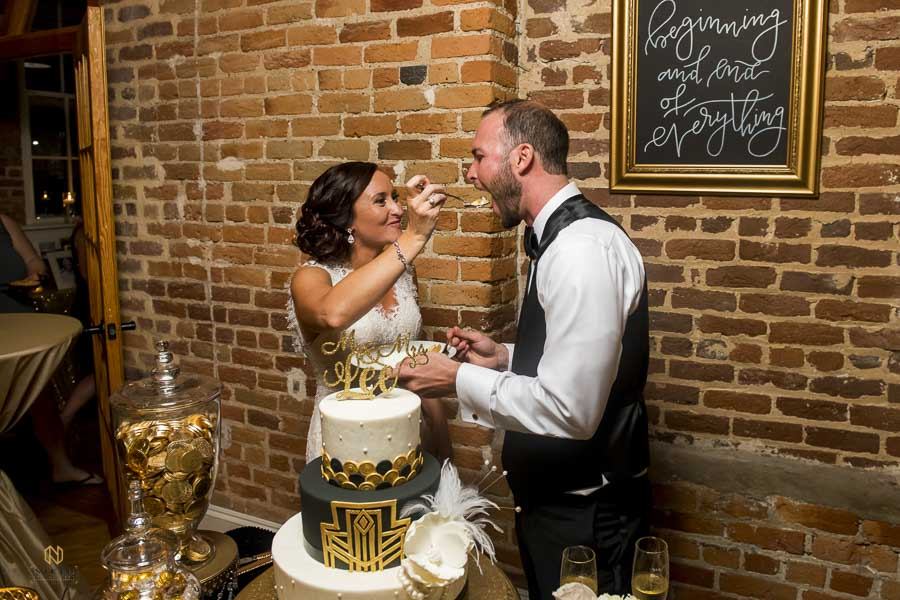 bride feeding the groom cake as he makes a face before he closes his mouth