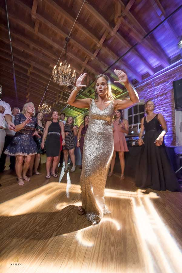 bridesmaid in a gold dress raising her arms up on the dance floor at Melrose Wedding Mill