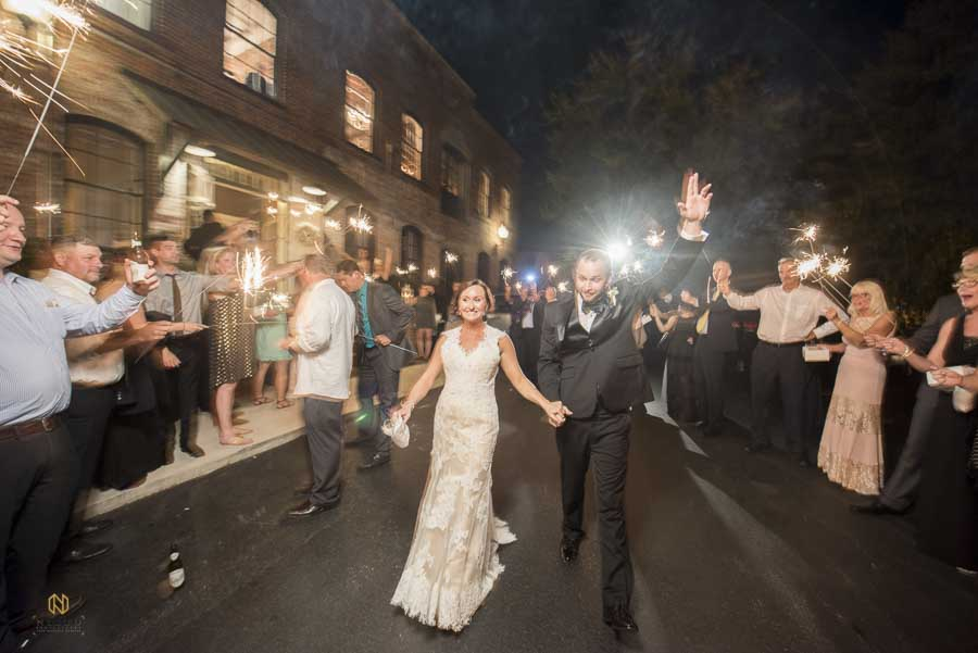 bride and groom walking through their sparkler exit at Melrose Knitting Mill