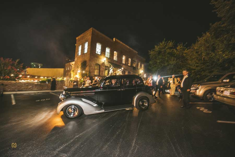 vintage car pulling away from a Melrose Knitting Mill wedding at night