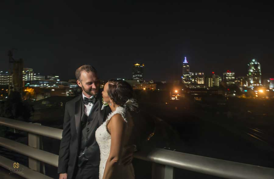Bride and groom posing on boylan bridge at night with the city of raleigh lit up behind them