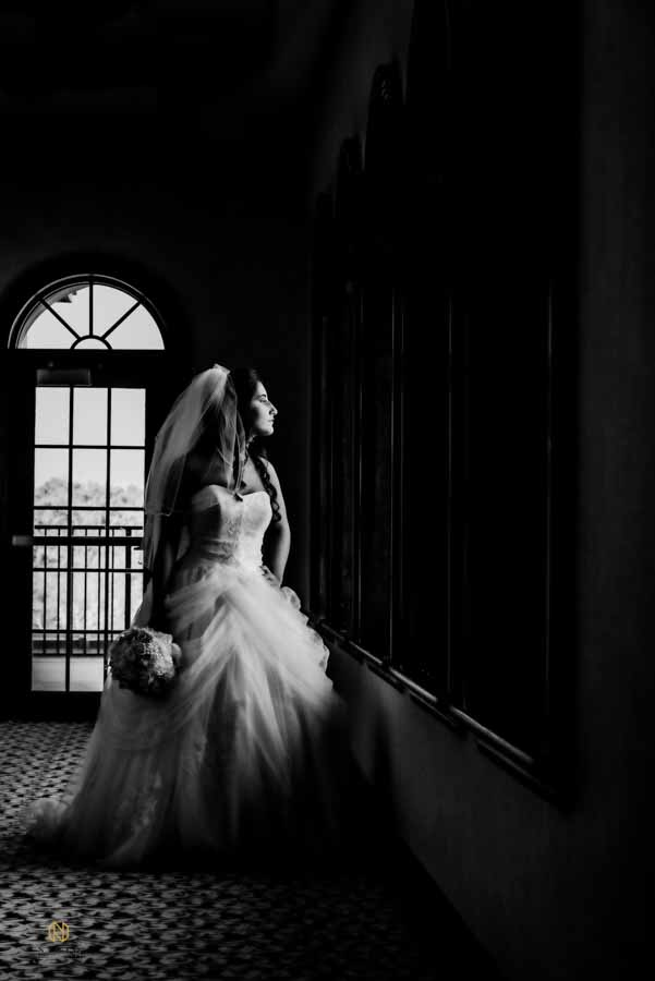 black and white image of bride looking out a window while she holds her bridal bouquet