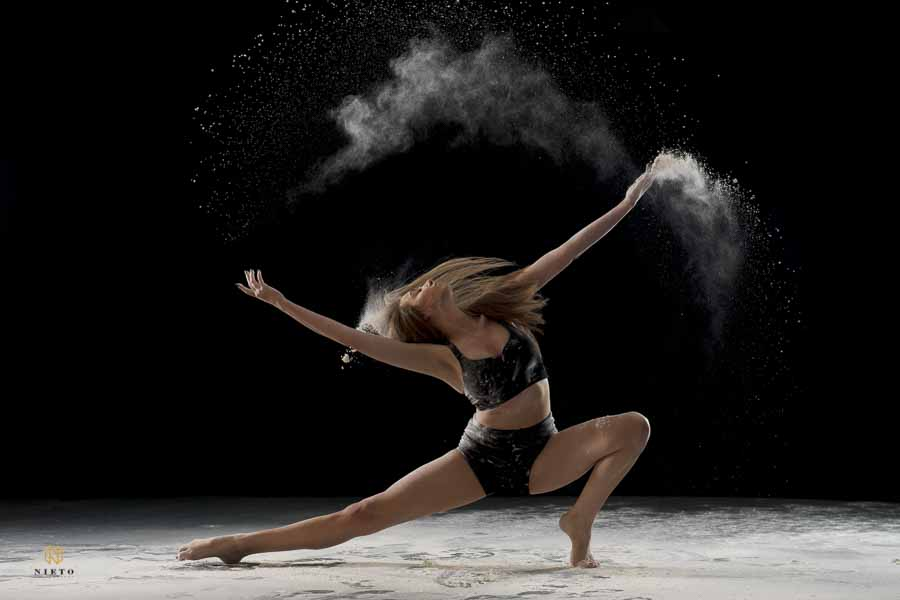 dancer crouching as she throws flour for a creative dance shoot