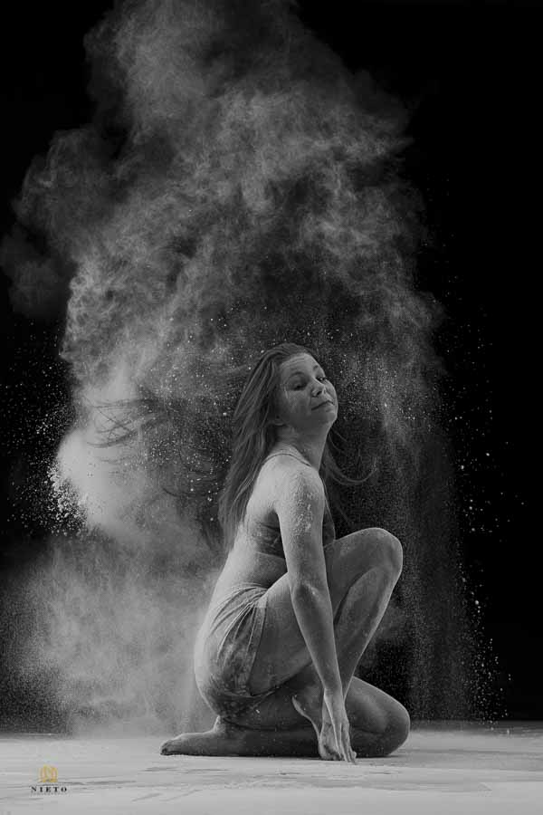 black and white picture of a dancer covered in flour as she is flipping her hair