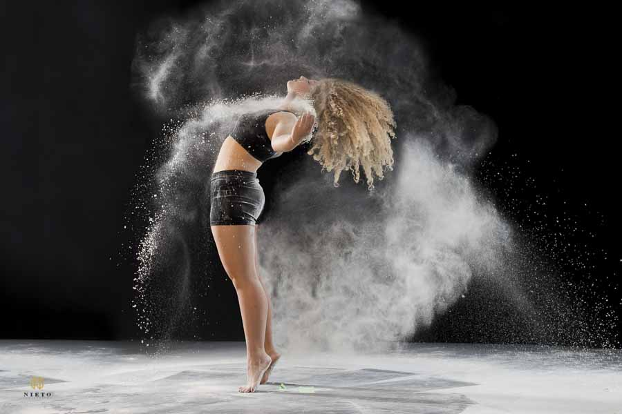 side view of a dancer standing on her toes throwing dust