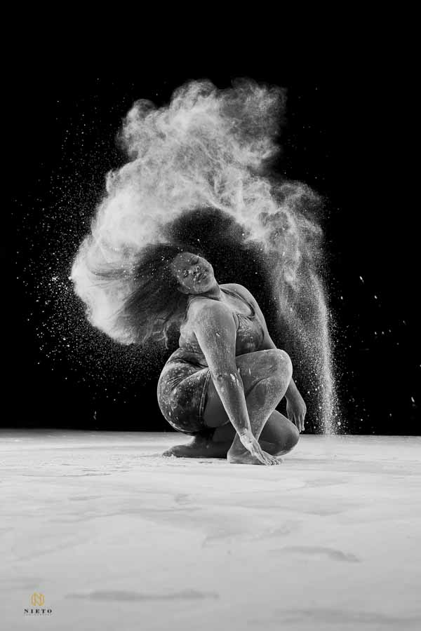 black and white picture of a dancer tossing her head back with flour arching over her head