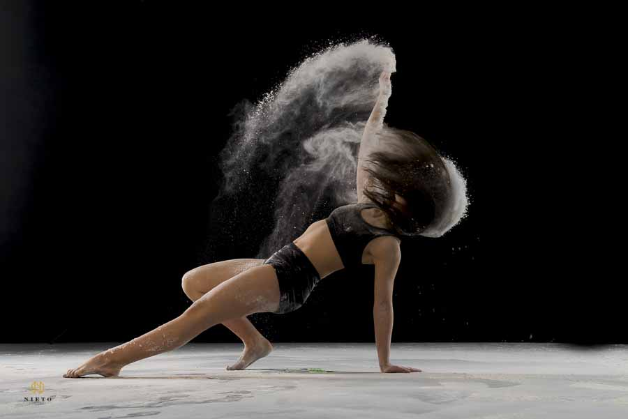 dancer leaning back as she throws dust behind her and she is flipping her hair
