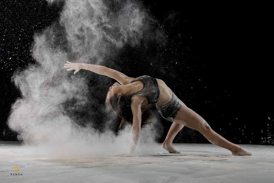 dancer supporting herself on one arm as she throws dust behind her