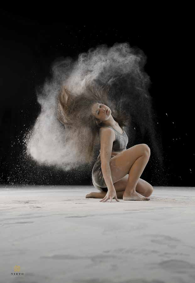 dancing crouching down as she flips her hair and dust comes flying from it