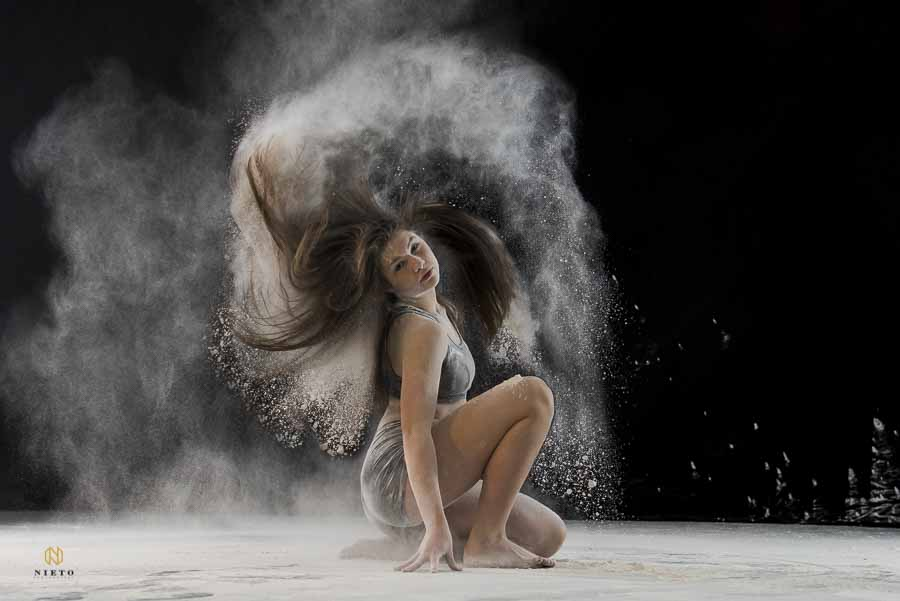 dancer looking at the camera as she flips her hair and dust comes flying from it.