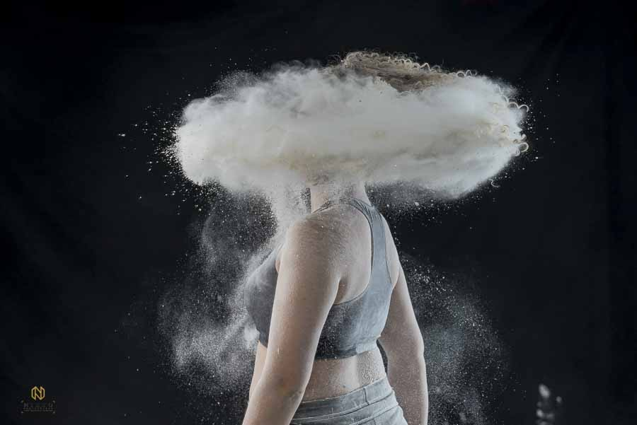 creative shoot of a model twirling with flour coming out of her hair