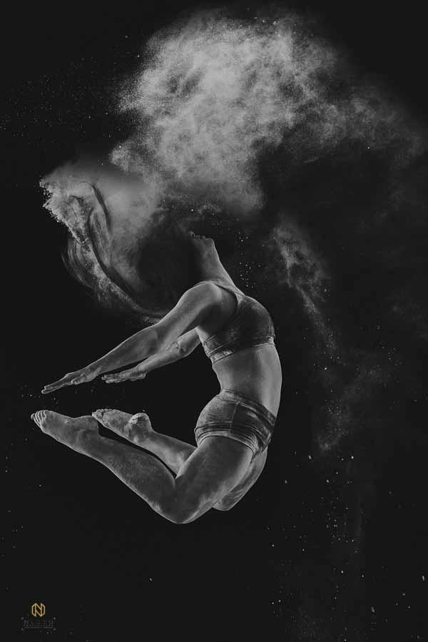 black and white image of a dancer leaping with her arms and legs behind her and flour coming from her hair