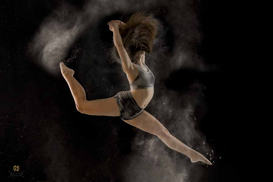 dancer leaping in the air as her hair covers her face and flour surrounds her body
