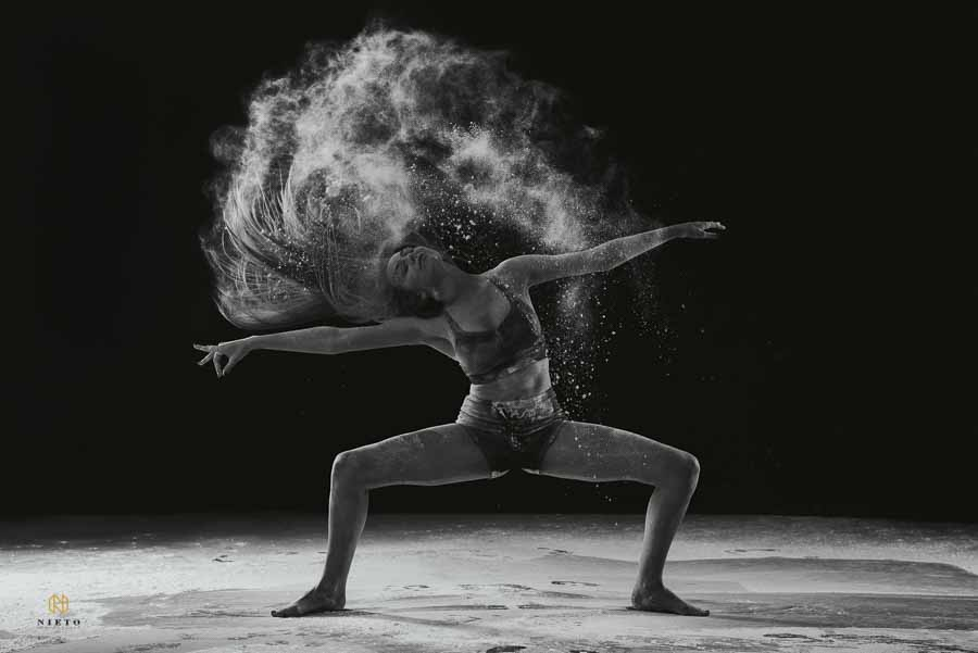 black and white image of a dancer flipping her hair while dust flies from her hair with flour all over the floor around her