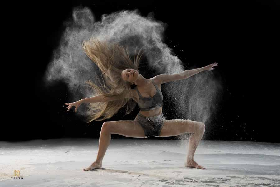 color image of a dancer flipping her hair while dust flies from her hair and her legs are in a 90 degree angle