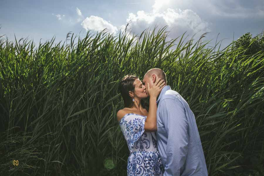 Couple kissing in front of the tall grass at the Whale Head Club in the OBX