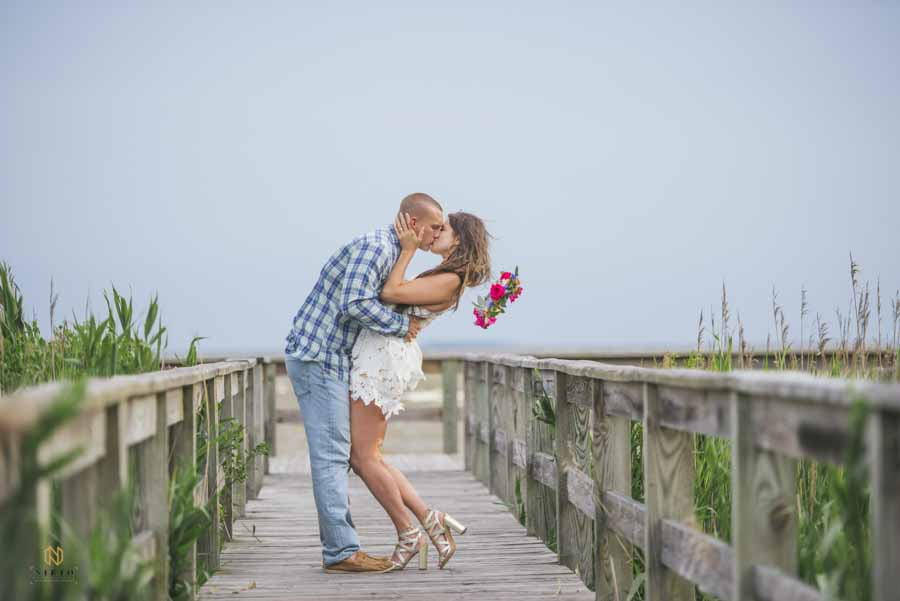 couple kissing on dock while woman flower crown flies off at the OBX