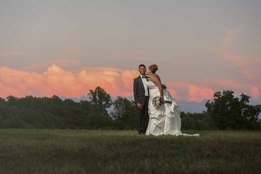 bride kissing her groom on the cheek at sunset in a field
