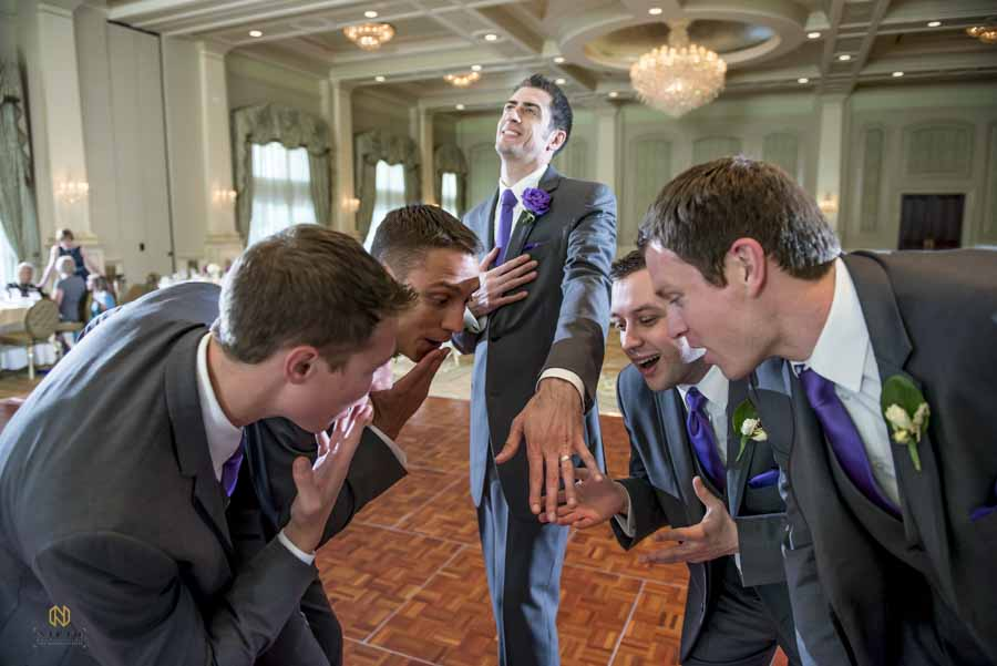 groom showing off his wedding band to his groomsmen inside of Preston Wood Country Club