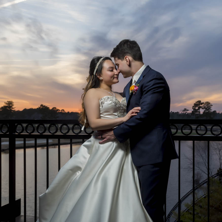 Couple about to kiss at River Landing Country Club with the sunsetting behind them