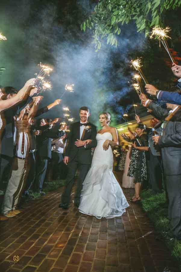 Bride and groom smiling as they exit through their sparkler exit at Rose Hill