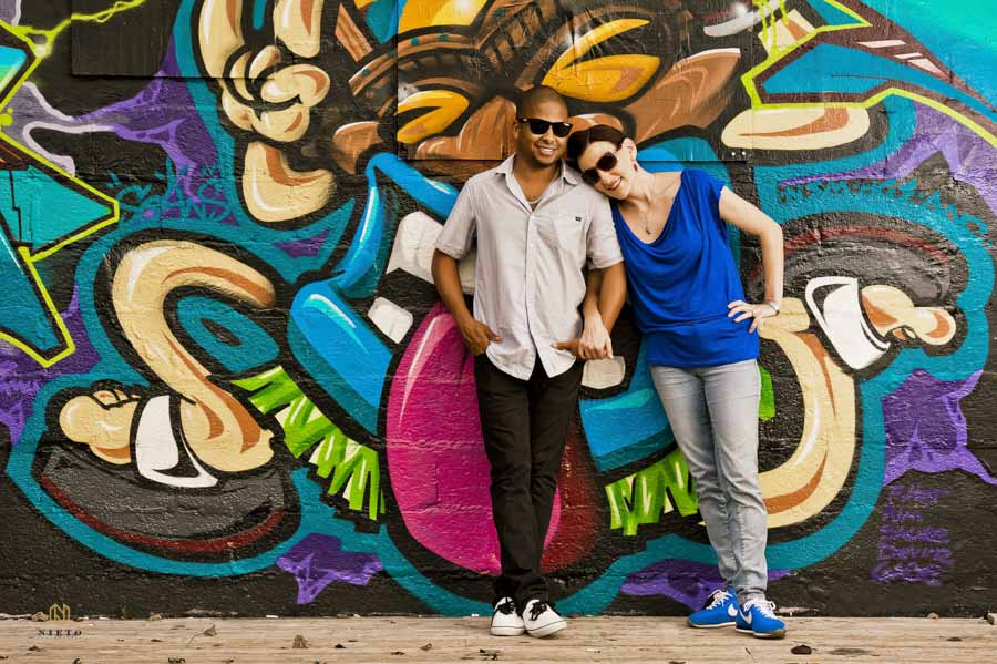 couple leaning against a graffiti wall in downtown raleigh posing for a portrait