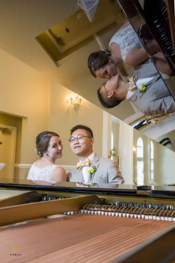 bride and groom posing for their raleigh wedding portraits while sitting at a piano with reflection