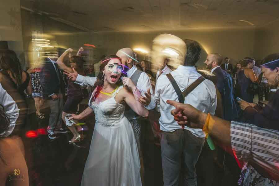 Bride dancing with wedding guest with glow sticks at the Garden on Millbrook
