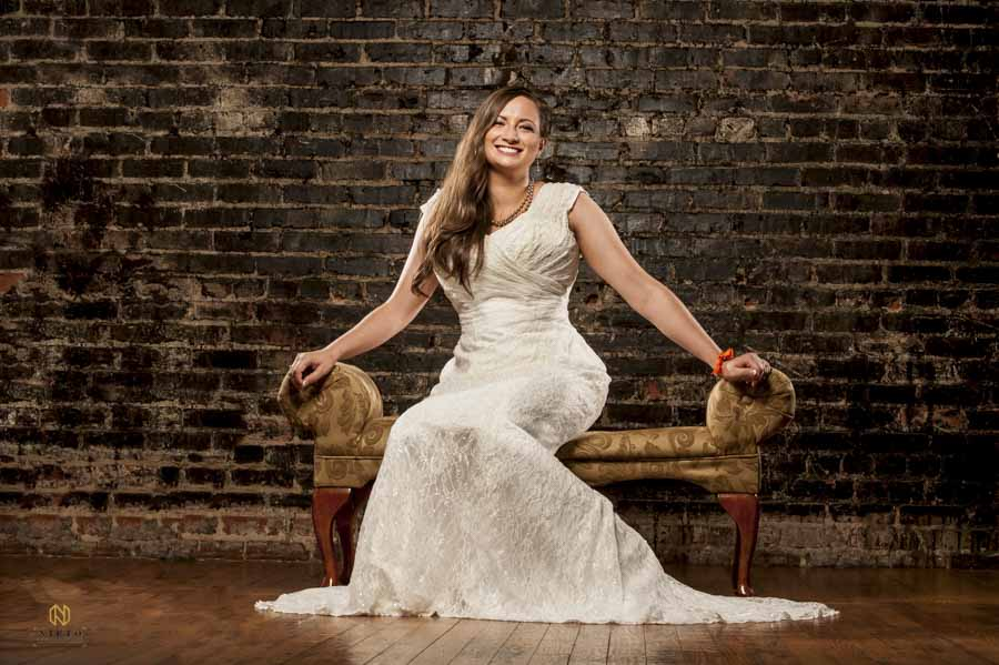 bride smiling as she sits on an antique chair against a brown brick wall