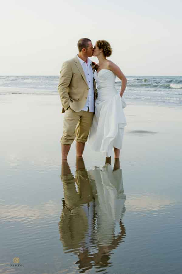 bride and groom kissing as the stand in the ocean after their wedding ceremony