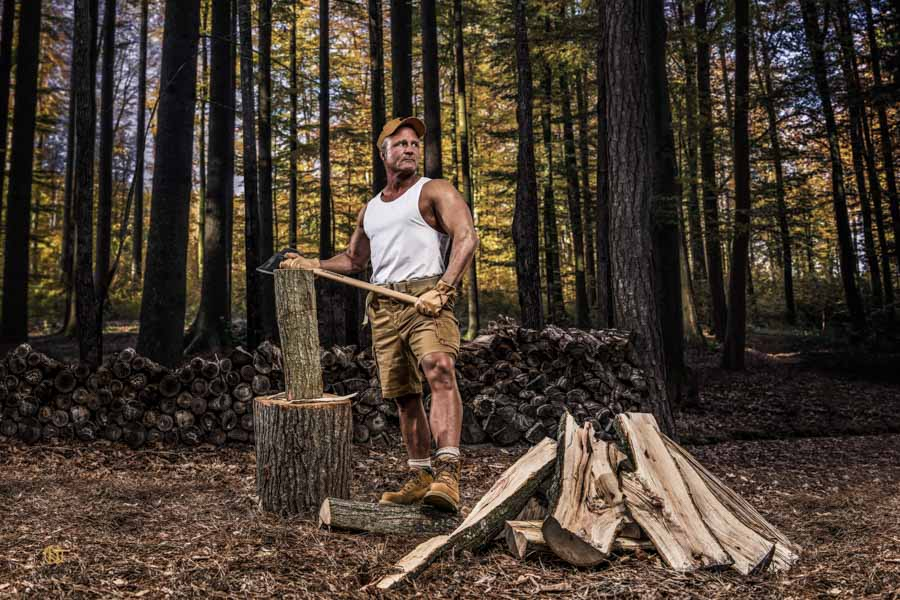 Fitness model looking off in the distance as he is chopping wood