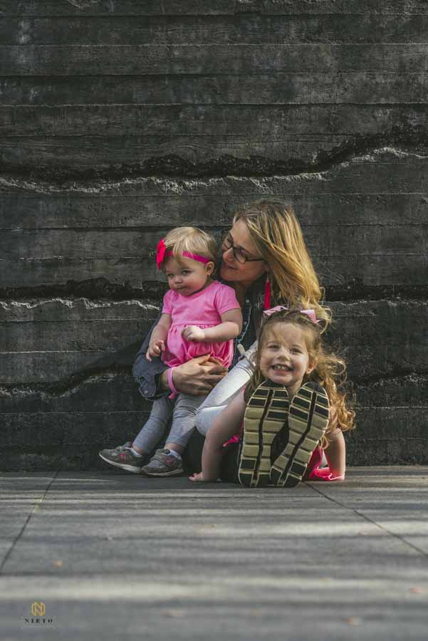 mother and daughters sitting together in front of a stone wall at the NC Museum of Art