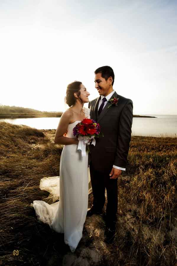Bride and groom smiling at each other as they pose together after their OBX wedding